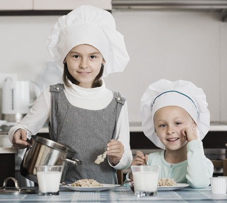 Two little friends  having breakfast with oatmeal porridge indoors Stock Photo