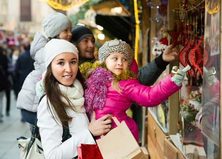 Happy young parents with two little daughters choosing decorations at X-mas market. Focus on woman