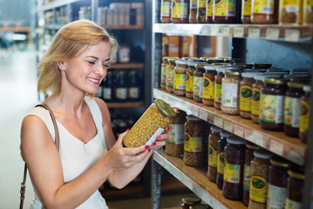 Portrait of happy positive woman buying conserve peas in glass jar in grocery shop Stock Photo