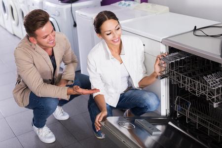 middle class: familia de clase media seleccionando lavavajillas moderna en hipermercados y sonriente
