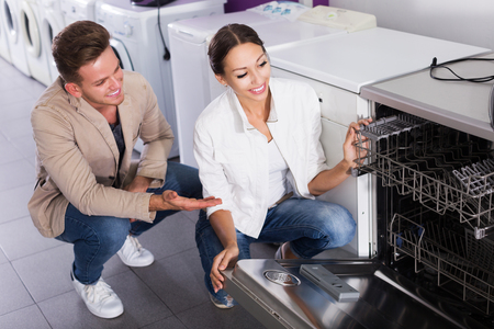 middle class: Middle class family selecting modern dishwasher in hypermarket and smiling