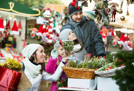 Ordinary happy family with little girls standing at a coniferous Christmas souvenirs counter. Focus on women and child in magenta clothes