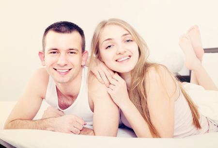 Happy young loving couple lounging in bed after awaking cuddling