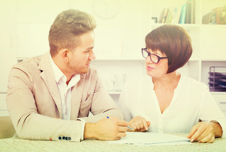 Happy young man and mature woman sit at table and discuss legal aspects of paperwork Stock Photo
