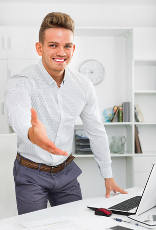 Happy smiling  businessman offerring hand for greeting in office interior