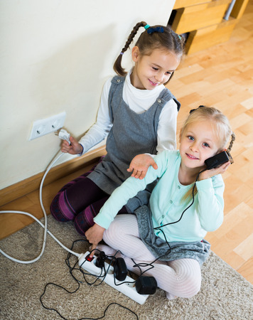 sockets: positive european children playing with sockets and electricity indoors