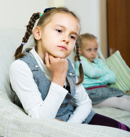 Offended little sisters sitting on sofa apart of each other after argue Stock Photo