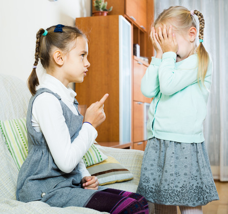 berate: Serious russian girl lecturing little sister in domestic interior Stock Photo