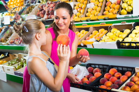 laughing positive woman with girl buying ripe peaches in food store Stock Photo