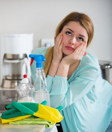 Exhausted young housewife taking a break as cleaning in kitchen