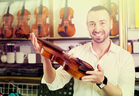 Young cheerful man with beard purchasing traditional violins in store Stock Photo