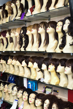 wigs: Mannequins with colorful wigs types on shelves of hair salon Stock Photo