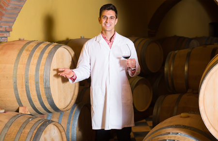 laboratorian: happy man in white robe checking ageing process of red wine Stock Photo