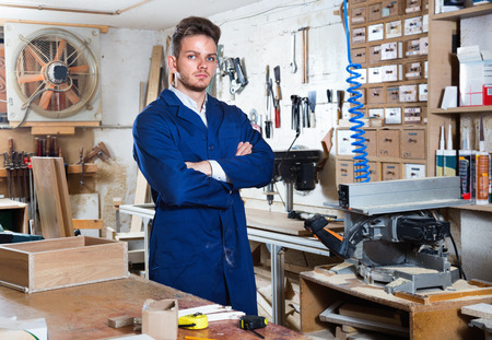 displaying: Glad  positive guy displaying his workplace and tools at workshop Stock Photo
