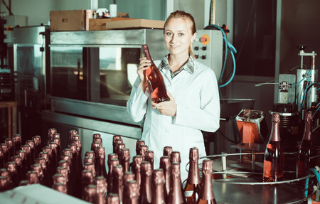 woman holding newly produced bottles of wine on winery manufactory Stock Photo