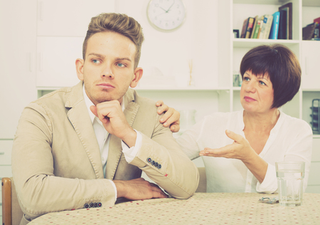 persuade: Elderly woman tries to persuade young man dont worry Stock Photo
