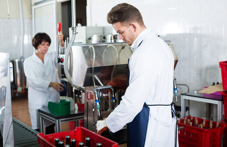 producing: Worker bottling sparkling wine with machine at wine factory Stock Photo