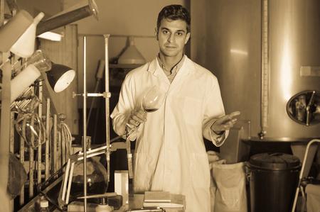 white robe: Efficient technician in white robe controlling fermantation process of wine