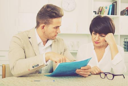 diligente: El hombre hermoso joven diligente discute la corrección de papeleo con compañero de trabajo