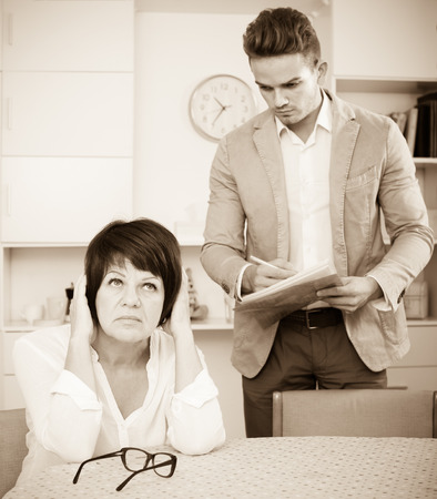 Adult woman has discontentedly turned away from man who suggests her to sign documents Stock Photo