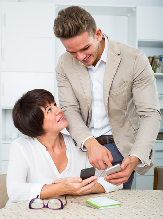 specifies: Son telling his elderly mother how to use phone