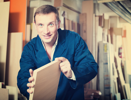 picture framing: positive male worker standing with plywood pieces in picture framing workshop Stock Photo