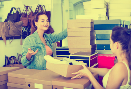 seller: happy teenager girl taking box with chosen pairs from seller in shoes boutique