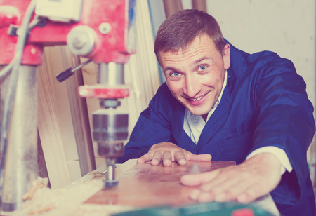 portrait of happy european man in uniform working with electrical screwdriver on plywood indoors Stock Photo