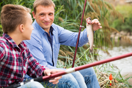 gudgeon: Portrait of cheerful father with teenager son having fish in hands outdoors Stock Photo