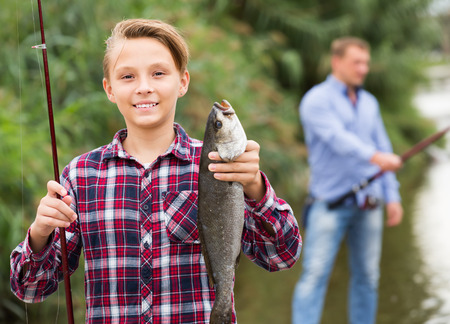 Portrait of laughing teenager boy having fish in hands outdoors