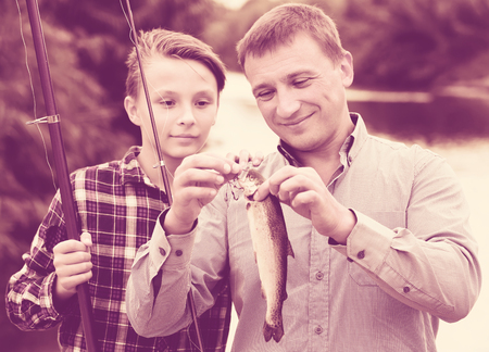 Glad teenage boy and his father holding taken freshwater fish in hands
