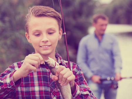 gudgeon: Intrested teenage boy releasing catch on hook fish outdoors Stock Photo