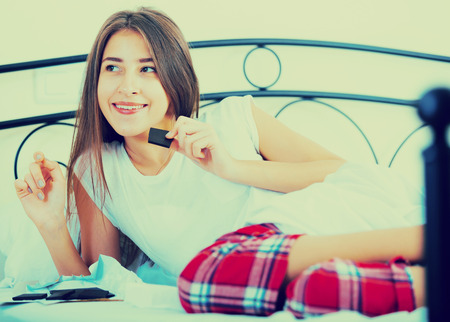 Happy girl sitting in bed and eating dark chocolate indoors Stock Photo