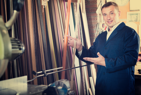 picture framing: cheerful male seller standing in picture framing studio with wooden details