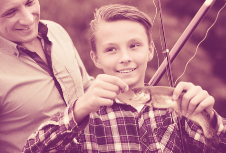 Portrait of happy man with teenager son looking at fish on hook in hands outdoors