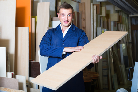picture framing: portrait of happy american  man in uniform choosing tight wooden bar in picture framing atelier