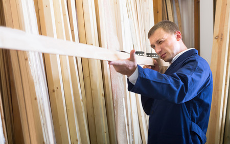 picture framing: portrait of happy european  man in uniform choosing compressed densified wood in picture framing atelier Stock Photo