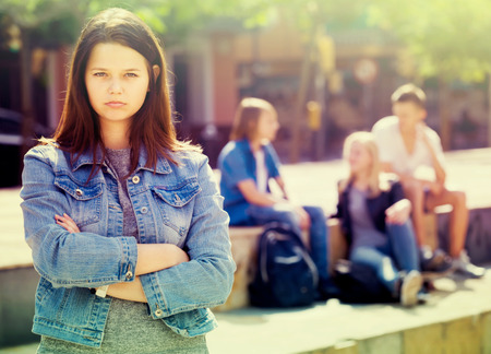 lonely female teenager standing away from friends feeling depressed