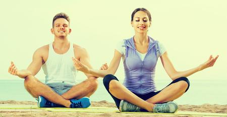 crosslegged: Cross-legged russian  couple practice yoga on beach in morning Stock Photo