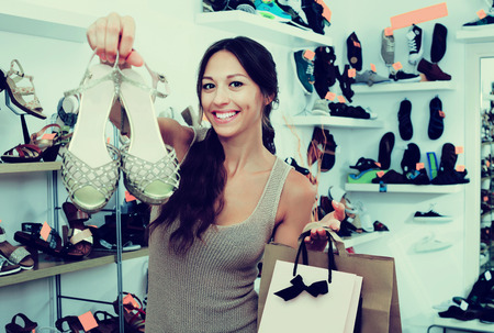 chosen: Happy young woman standing in boutique with shopping bags and chosen shoes in boutique