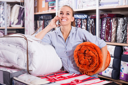 coverlet: Happy woman with mobile shopping new blanket and coverlet in textile store Stock Photo