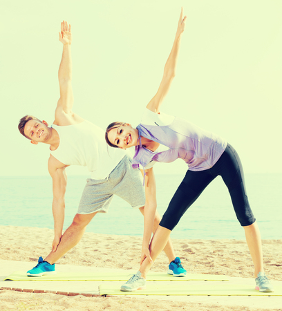 Positive man and woman training on beach by sea on sunny morning