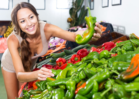 Portrait of young happy woman customer buying organic peppers in food store Stock Photo