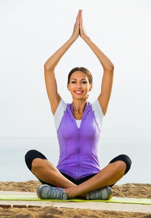 crosslegged: Smiling cheerful  woman doing youga training cross-legged on beach on  sunny day