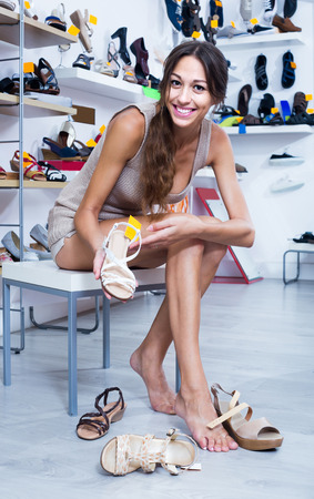 chosen: happy girl customer trying on chosen shoes in footwear department Stock Photo