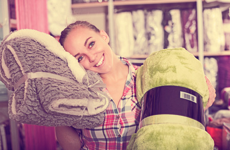 coverlet: Young woman choosing new coverlet for home in textile shop Stock Photo