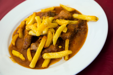 Goulash served with potato chips in rich meat gravy Stock Photo