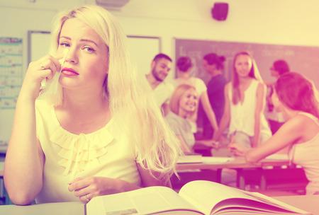 bulling: Llorando la hermosa rubia sentado en el aula de la universidad en la mesa cerca de un libro de texto