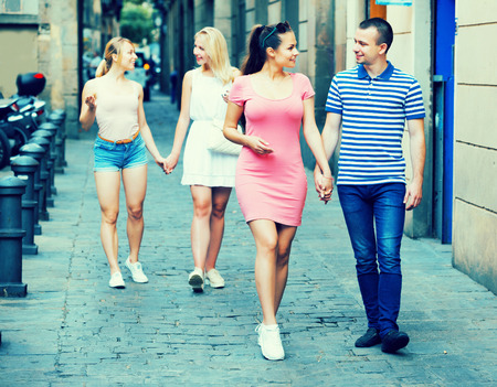 astonishing: Positive young couple walking and looking around in summer city Stock Photo