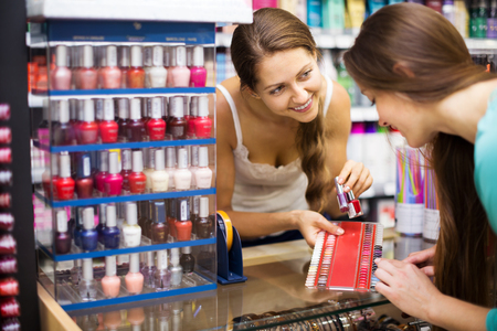 store clerk: Smiling store clerk serving purchaser with nail polish in the shopping mall Stock Photo